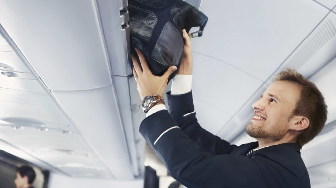 Finnair flight attendant assisting with hand luggage in business class