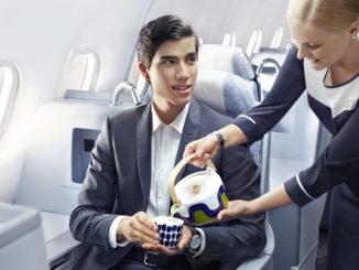 Finnair flight attendant pouring green tea to a man in business class