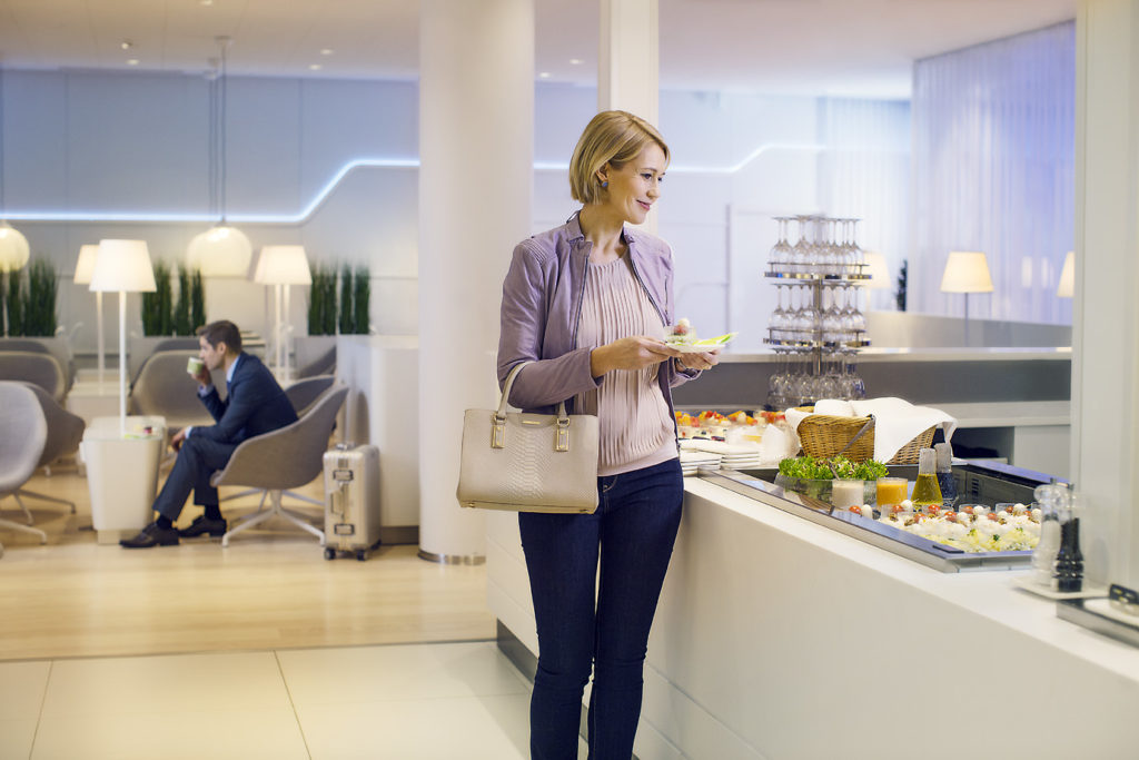 Finnair new Premium Lounge Helsinki Vantaa woman taking food from the buffet