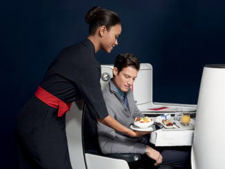 Air France new business class seat - male passenger during meal service being served by a flight attendant