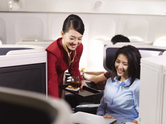 Cathay Pacific Business Class cabin and seat with flight attending serving drink