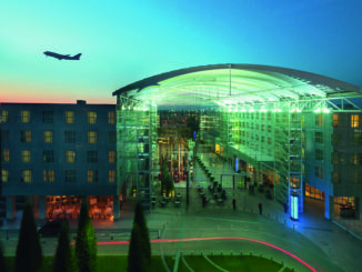 Hilton Munich Airport Hotel exterior with aircraft taking off