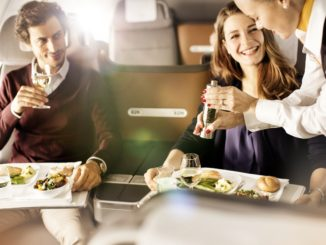 Passengers are offered pepper by a Lufthansa flight attendant during the meal service in business class