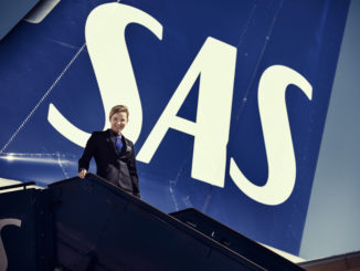 SAS flight attendant in the new uniform in front of aircraft tail with logo