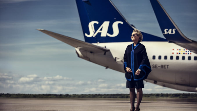 SAS flight attendant with the new uniform in front of a Boeing 737